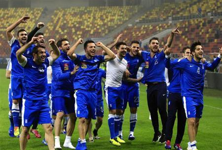 Greece's players celebrate defeating Romania during their 2014 World Cup qualifying soccer match in Bucharest November 19, 2013. REUTERS/Radu Sigheti