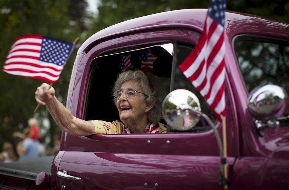 A woman waves an American flag as she rides in an antique pickup truck through Barnstable Village on Cape Cod, during the annual Fourth of July Parade celebrating the country's Independence Day, i