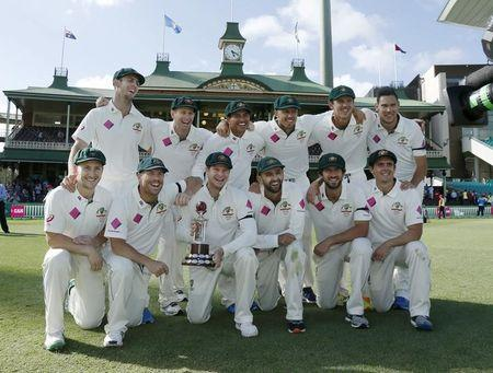 Australia's test cricket captain Steve Smith holds the Frank Worrell trophy among team mates after their third cricket test against the West Indies at the SCG in Sydney