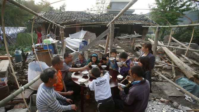In this Monday, April 22, 2013 photo, villagers have dinner near their home, damaged by Saturday's earthquake, in Lushan county of southwest China's Sichuan province. The efforts under way in mountainous Sichuan province after the quake Saturday that killed at least 192 people showed that the government has continued to hone its disaster reaction - long considered a crucial leadership test in China - since a much more devastating earthquake in 2008, also in Sichuan, and another one in 2010 in the western region of Yushu. (AP Photo) CHINA OUT