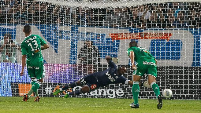 Saint-Etienne's French defender Faouzi Ghoulam, left, scores a penalty against Marseille's French goalkepper Steve Mandanda during their League One soccer match, at the Velodrome Stadium, in Marseille, southern France, Tuesday, Sept. 24, 2013