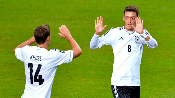 Germany's Mesut Ozil, right, celebrates scoring his team's first goal with team mate Max Kruse during the 2014 World Cup group C qualifying soccer match between Sweden and Germany at Friends Arena in Stockholm, Sweden, Tuesday, Oct. 15, 2013