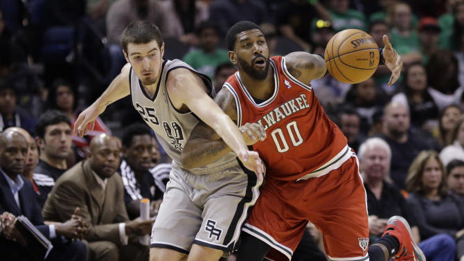 San Antonio Spurs' Nando De Colo (25), of France, and Milwaukee Bucks' O.J. Mayo (00) chase down a loose ball during the second half of an NBA basketball game, Sunday, Jan. 19, 2014, in San Antonio. San Antonio won 110-82