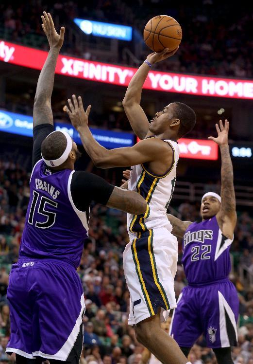 Sacramento Kings' DeMarcus Cousins (15) and Sacramento Kings' Isaiah Thomas (22) defend as Utah Jazz's Alec Burks, center, takes a shot in the second half of an NBA basketball game on Saturday, Dec. 7, 2013, in Salt Lake City. The Kings went on to win 112-102 in overtime