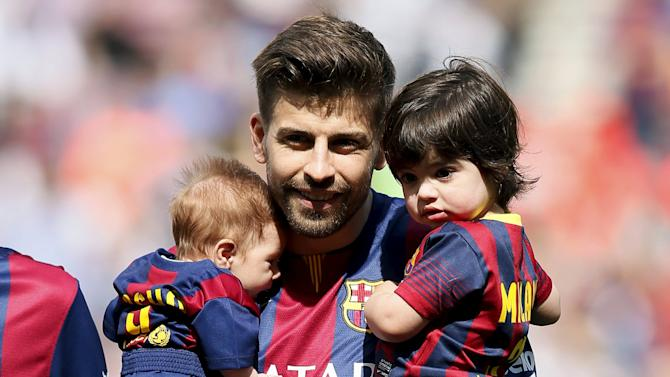 Barcelona's soccer player Gerard Pique holds his sons Sasha and Milan before the Spanish first division soccer match between Barcelona and Valencia at Camp Nou stadium in Barcelona