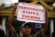 An ethnic Rakhine demonstrator holds a sign as hundreds protest at Yangon's Shwedagon pagoda after unrest flared in the western Myanmar state. Security forces have tried to restore order to a Myanmar state placed under emergency rule after a wave of deadly religious violence, as the United Nations evacuated foreign workers