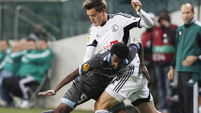 Rachid Hamdani, left, of Apollon Limassol FC challenges for the ball with Michal Zyro , right, of Legia Warsaw, during their Europa League group J soccer match in Warsaw, Poland, Thursday, Oct. 3, 2013