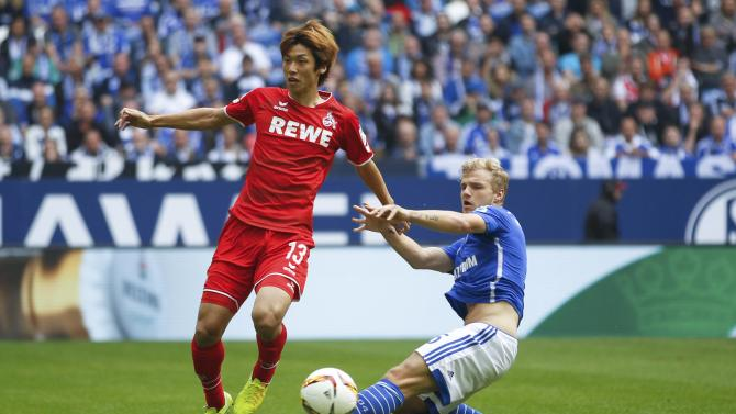 Schalke 04's Geis challenges 1.FC Cologne's Osako during their Bundesliga first division soccer match in Gelsenkirchen