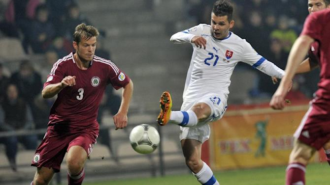 Latvia's Renars Rode, left, challenges Slovakia's Michal Duris for the ball during a World Cup 2014 Group G qualification match in Riga, Latvia, on Tuesday Oct. 15, 2013