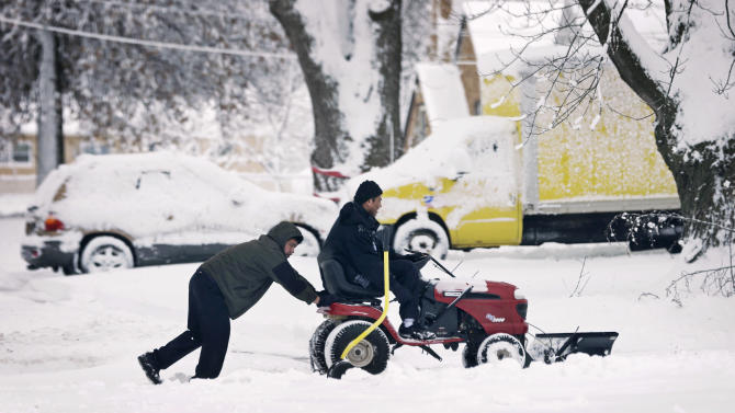 Victor Jimenez, of Des Moines, Iowa, gets a push from his dad Guillermo Jimenez, left, as they clear snow off a driveway, Thursday, Dec. 20, 2012, in Des Moines, Iowa. The first widespread snowstorm of the season began a slow crawl across the Midwest on Thursday with some areas receiving as much as 15 inches of snow. (AP Photo/Charlie Neibergall)