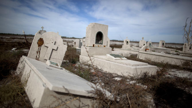 In this May 7, 2013 photo, tombs lay in the ruins of Epecuen, a village that was submerged in water in Argentina. When a particularly heavy rainstorm followed a series of wet winters, the lake overflowed its banks on Nov. 10, 1985. Water burst through a retaining wall and submerged the lakeside streets. People fled with what they could, but a few days later, their homes were drowned under nearly 10 meters (33 feet) of corrosive saltwater. (AP Photo/Natacha Pisarenko)
