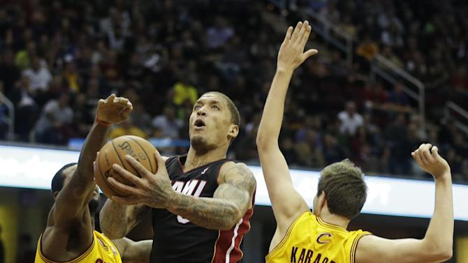 Miami Heat's Michael Beasley shoots between Cleveland Cavaliers' Earl Clark and Sergey Karasev (10) in the fourth quarter of an NBA basketball game Wednesday, Nov. 27, 2013, in Cleveland. The Heat won 95-84