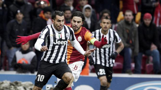 Tevez of Juventus challenges Inan of Galatasaray as mounds of snow are on display in the background.