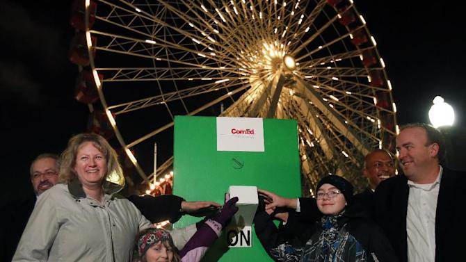 In this photo provided by ComEd, from left, Senior Vice President of ComEd Fidel Marquez, ComEd customer Kathy Reiser, her children Caitlin and Ramsey, Navy Pier director of External Communications Nick Shields and Ald. Brendan Reilly, 42 Ward, pose for a photo as they turn off the lights of the Ferris Wheel at Navy Pier in observation of Earth Hour in Chicago on Saturday, March 23, 2013. (AP Photo/ComEd, Charles Osgood)