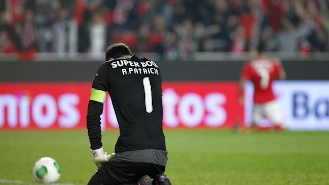 Sporting's goalkeeper Rui Patricio kneels down as Benfica's Oscar Cardozo, background right, from Paraguay, celebrates after scoring past Patricio during a Portugal Cup soccer match between Benfica and Sporting at Benfica's Luz stadium in Lisbon, Saturday, Nov. 9, 2013. Benfica won 4-3 in extra time