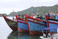 In this photo taken Wednesday, June 10, 2015 and released by the Government of the Republic of Palau, Vietnamese fishermen sit on their fishing ships anchored at the Marine Law Enforcement Division Port in Koror, Palau after being caught fishing illegally in the waters of the country. The tiny Pacific nation of Palau, fighting a rising tide of illegal fishing in its waters, has set fire to four boats of Vietnamese caught poaching sea cucumbers and other marine life in its waters. Palau's president, Tommy Remengesau Jr., said the boats were burned Friday morning, June 12, 2015. He hopes to turn most of the island nation's territorial waters into a national marine sanctuary, banning commercial fishing and exports apart from limited areas to be used by domestic fishermen and tourists. (The Government of the Republic of Palau via AP)
