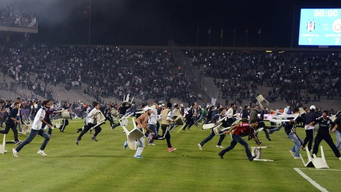 Besiktas fans throw chairs and run onto the pitch during the Turkish Super League derby soccer match between Besiktas and Galatasaray in Istanbul