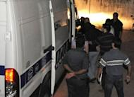 Police escort a suspect (C) in the killing of patients in a care center scandal in Uruguay to a van. The killings, which could number into the hundreds, may date back as far as 2010, according to the court testimony of one of the accused nurses
