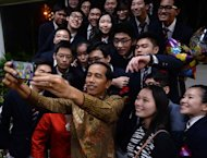Indonesian President Joko Widodo takes a selfie with classmates of his youngest son Kaesang Pangarep, at the Anglo-Chinese International School in Singapore, on November 21, 2014