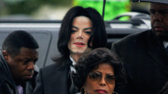 FILE - In this Monday, Feb. 28, 2005 file photo, Michael Jackson follows his mother, Katherine Jackson, as they arrive for court on the opening day of his child molestation trial at Santa Barbara County Superior Court in Santa Maria, Calif. Opening statements are scheduled to begin Monday April 29, 2013, in Katherine Jackson's lawsuit against concert giant AEG Live over Michael's 2009 death. Katherine Jackson claims the company failed to properly investigate the doctor who was convicted in 2011 of involuntary manslaughter for the singer's death, but the company denies all wrongdoing. (AP Photo/Marcio Jose Sanchez, File)