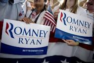 """Supporters hold campaign signs as US Republican presidential candidate Mitt Romney and his running mate Paul Ryan speak at a campaign rally in Manassas, Virginia, on August 11. Romney and Ryan will try to energize supporters in North Carolina Sunday after they hit the road on a bus tour across must-win US states, selling themselves as the duo who can """"save the American dream."""""""