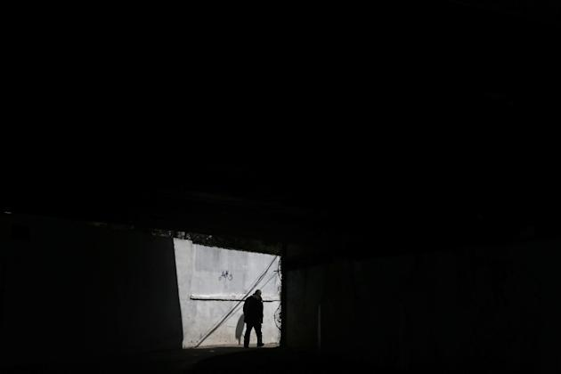 A man walks under a bridge in central Athens on Monday, March 30, 2015.  Greece and its international creditors are still struggling to agree on a list of economic reforms that are deemed necessary fo