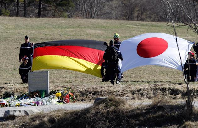 The German, left, and Japanese flags are deployed during an homage ceremony with  family members of Japanese victims in front of a stele, a stone slab erected as a monument, set up in memory of the vi