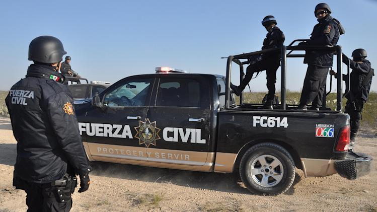 Nuevo Leon state police stand guard on a dirt road leading to a ranch near the town of Mina, in northern Mexico, Monday, Jan. 28, 2013. At least eight bodies were found in a well near this ranch on Sunday near the site where 20 people went missing late last week, including members of a Colombian-style band, according to a state forensic official. Officials could not confirm whether the bodies belonged to 16 members of the band Kombo Kolombia and their crew, who were reported missing late last week after playing a private show in a bar in the neighboring town of Hidalgo north of Monterrey. (AP Photo/Emilio Vazquez)