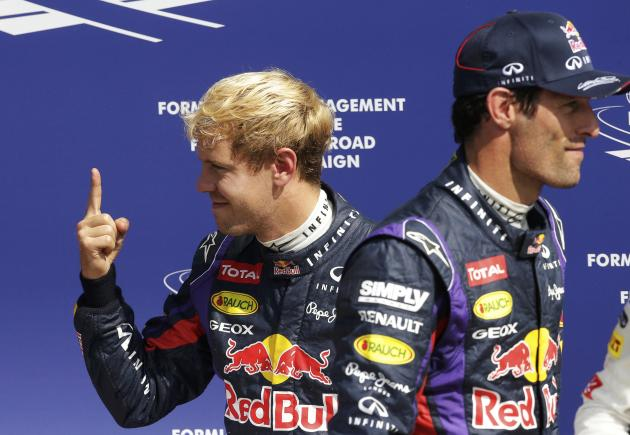 Red Bull Formula One driver Vettel celebrates taking the pole position, as team mate Webber walks past, after the qualifying session of the Italian F1 Grand Prix at the Monza circuit