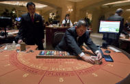 Baccarat dealer Ramiro Nepomuceno, right, shuffles cards as floor supervisor Sam Insyxiengmay looks on while preparing a table for play at the MGM Hotel and Casino, Wednesday, Jan. 25, 2012, in Las Vegas. There are generally more Asian gamblers in Vegas because of the Chinese New Year, and it means increased traffic at high limit baccarat tables. Though not widely known, baccarat is actually the most profitable table game for casinos which try to court Asian gamblers who tie luck and good fortune to the start of the Lunar Year. (AP Photo/Julie Jacobson)