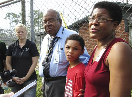 Tananarive Due, with her father John Due and her son, Jason Due-Barnes, speaks with reporters outside the gates of the now-closed Arthur Dozier School for Boys in Marianna