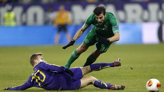 Wigan's Jordi Gomez, top, is tackled by Maribor's Ales Mertelj during their group D Europa League soccer match, in Maribor, Slovenia, Thursday, Dec. 12, 2013