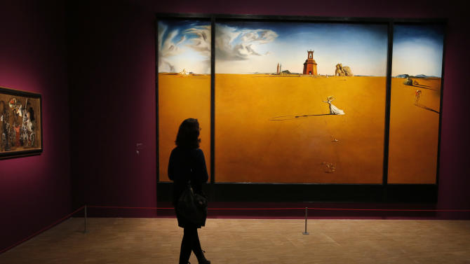 "In this photo taken Monday Nov. 19, 2012, a women looks at the painting 'Paysage avec jeune fille sautant a la corde, 1936' by Spanish artist Salvador Dali (1904-1989) during the presentation to the press of the exhibition ""Dali"" at the Centre Pompidou modern art museum, in Paris. A major retrospective of Salvador Dali in Paris aims to rewrite the art history books, reconciling for the first time the last decades of his life _ when he was accused of money-making self-publicity through numerous television appearances _ with his earlier, respected Surrealist period. (AP Photo/Francois Mori)"