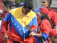 """Venezuelan President Nicolas Maduro dances with First Lady Cicilia Flores during a traditional May Day rally in Caracas on May 1, 2013. Maduro said Washington was making a """"grave mistake"""" in not acknowledging his victory in the controversial April 14 presidential election"""