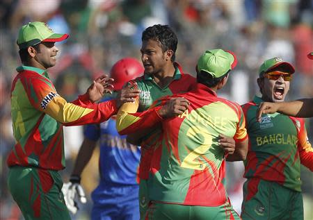 Bangladesh's Al Hasan reacts as other fielders congratulate him after dismissing Afghanistan's Tarakai successfully during ICC Twenty20 World Cup match in Dhaka