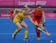 Jodie Schulz of Australia (L) fights for the ball with Zhao Yudiao of China during their women's field hockey match at the Riverbank Arena in London. Three-times Olympic champions Australia finished fifth in the women's hockey tournament after chiselling out a 2-0 win over China with with a hard-fought but sometimes rather toothless performance
