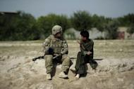 A US soldier of the 501st LABND Military Police Platoon speaks with an Afghan youth during a patrol in the village of Woro Keli, Buwri Tana district in Khost Province