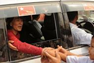 Myanmar opposition leader Aung San Suu Kyi greets supporters as she travels through the constituency where she is standing as a candidate in Kawhmu on April 1, 2012