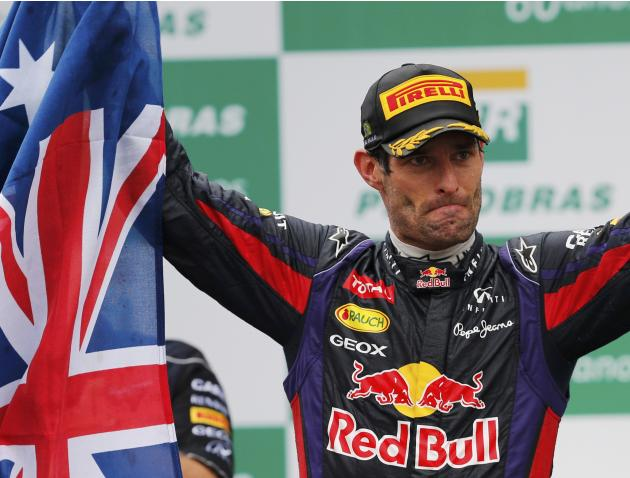 Mark Webber of Australia acknowledges the crowd as he holds up the Australian flag during podium celebrations after the Brazilian F1 Grand Prix at the Interlagos circuit in Sao Paulo