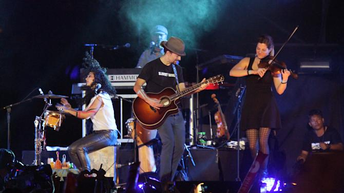 American singer-songwriter Jason Mraz, center, performs at the base of the famous hilltop Shwedagon Pagoda in Yangon, Myanmar, on Sunday, Dec. 16, 2012. Mraz mixed entertainment with education to become the first world-class entertainer in decades to perform in Myanmar, with a concert to raise awareness of human trafficking. (AP Photo/Zin Chit Aung)