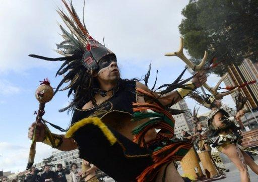 Dancers in costumes and head-dresses perform in Madrid in a ceremony marking the end of the Mayan age on December 21, 2012. A global day of lighthearted doom-themed celebration and superstitious scare-mongering culminated Friday in the jungle temples built by the Mayan people of Central America, whose calendar sparks fears of apocalypse.