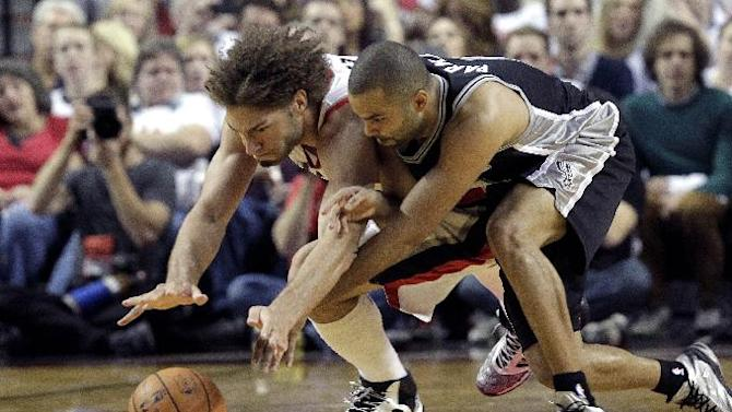 Portland Trail Blazers center Robin Lopez, left, and San Antonio Spurs guard Tony Parker dive for a loose ball during the second half of an NBA basketball game in Portland, Ore., Saturday, Nov. 2, 2013. Portland defeated San Antonio 115-105