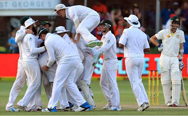 South Africa's players celebrate the winning wicket as Australia's batsman Nathan Lyon, right, watches on the fourth day of their 2nd cricket test match at St George's Park in Port Elizabe