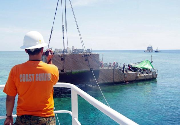 This photo, released on March 30, 2013 by Philippine Coast Guard (PCG), shows a portion of the stern of the USS Guardian being lifted by a boat crane during its salvage operation at Tubbataha reef, off Palawan island, western Philippines