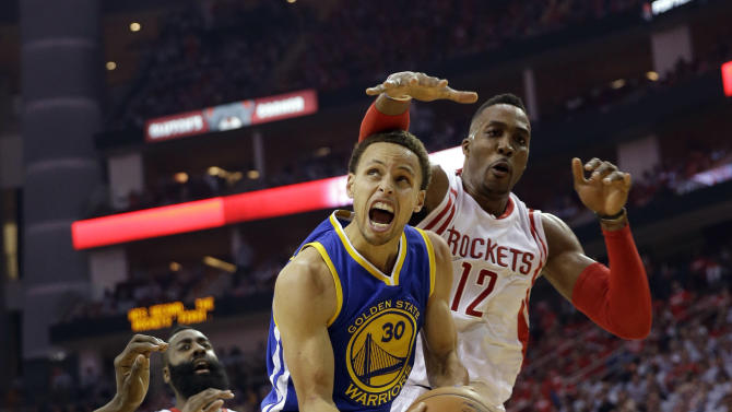 Golden State Warriors guard Stephen Curry (30) looks toward the basket before being fouled by Houston Rockets center Dwight Howard (12) during the first half in Game 3 of the NBA basketball Western Conference finals Saturday, May 23, 2015, in Houston. (AP Photo/David J. Phillip)
