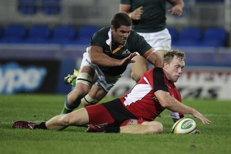 Mackenzie of Canada scores a try under the pressure of Hodgson of Australian Barbarians during their rugby union match in Gold Coast
