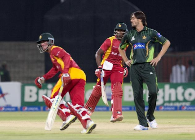 Zimbabwe's Vasimuzi Sibanda,  and  Sean Williams, left, run between the wickets as Pakistani bowler Anwar Ali looks on during a match at the Gaddafi Stadium in Lahore, Pakistan, Sunday, May 24, 20