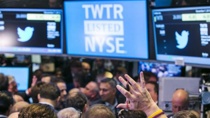A trader raises his hand just before the Twitter Inc. IPO begins on the floor of the New York Stock Exchange in New York