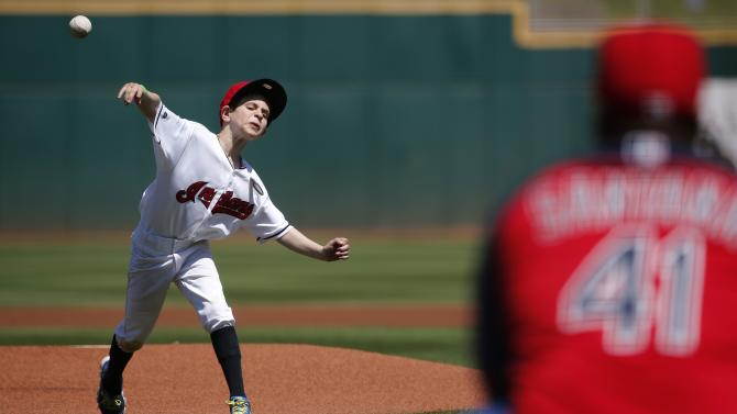 Cleveland Indians bat boy Jacob Bocock throws out the first pitch to Indians' Carlos Santana prior to a spring training baseball game against the Seattle Mariners Tuesday, March 31, 2015, in Goodyear, Ariz. (AP Photo/Ross D. Franklin)