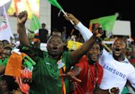 Zambian fans celebrate with the national flag after their team's victory over Ivory Coast in the Africa Cup of Nations (CAN) final match, at stade deI'Amite in Libreville, Gabon, on February 12, 2012. Chipolopolo won the tournament for the first time, just a few kilometres from where a military plane plunged into the sea and claimed the lives of almost all the 1993 Zambian national squad
